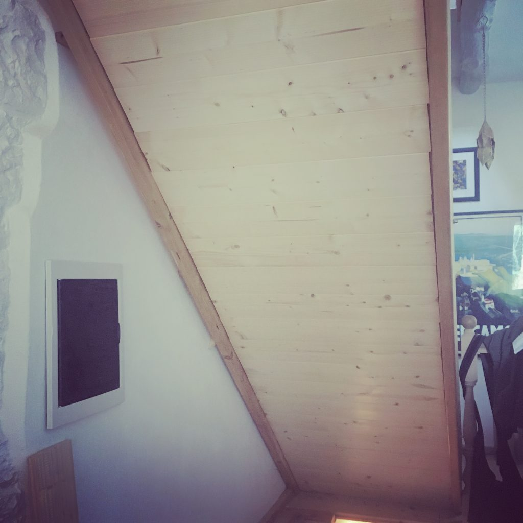 Pine boards attached to the frame of the stairs going to the upper floor
